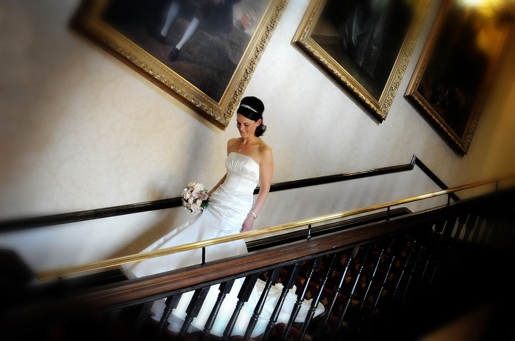 A beautiful bride watching her step as she descends the stairs on her way to get married at Wotton House, Dorking Surrey photo taken by Surrey Lane