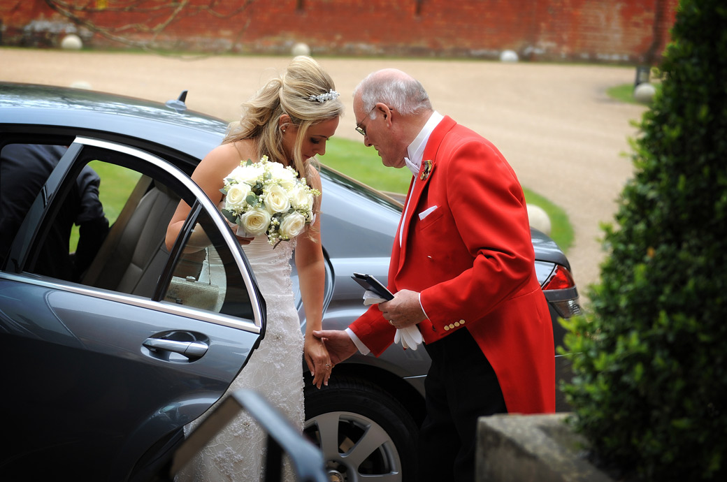 Bride is gently escorted from the bridal car by the master of ceremonies in this wedding photo take outside Wotton House a beautiful wedding venue in Dorking Surrey