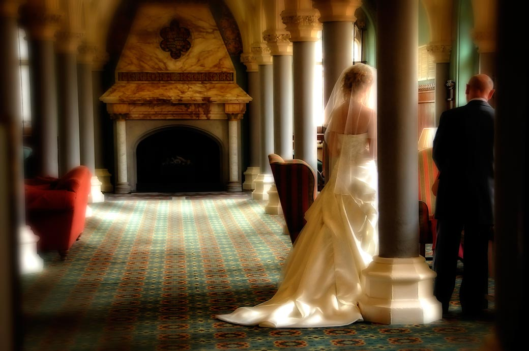 A discrete wispy wedding photograph of the Bride waiting to be interviewed by the registrar captured in the Old Library Wotton House Dorking  Surrey