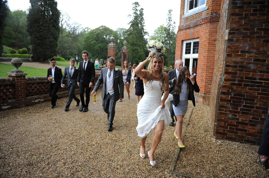Bride leads the wedding party with her dress hitched up and flower bouquet over her head out of the rain during the wedding photo session at Wotton House in Surrey Dorking