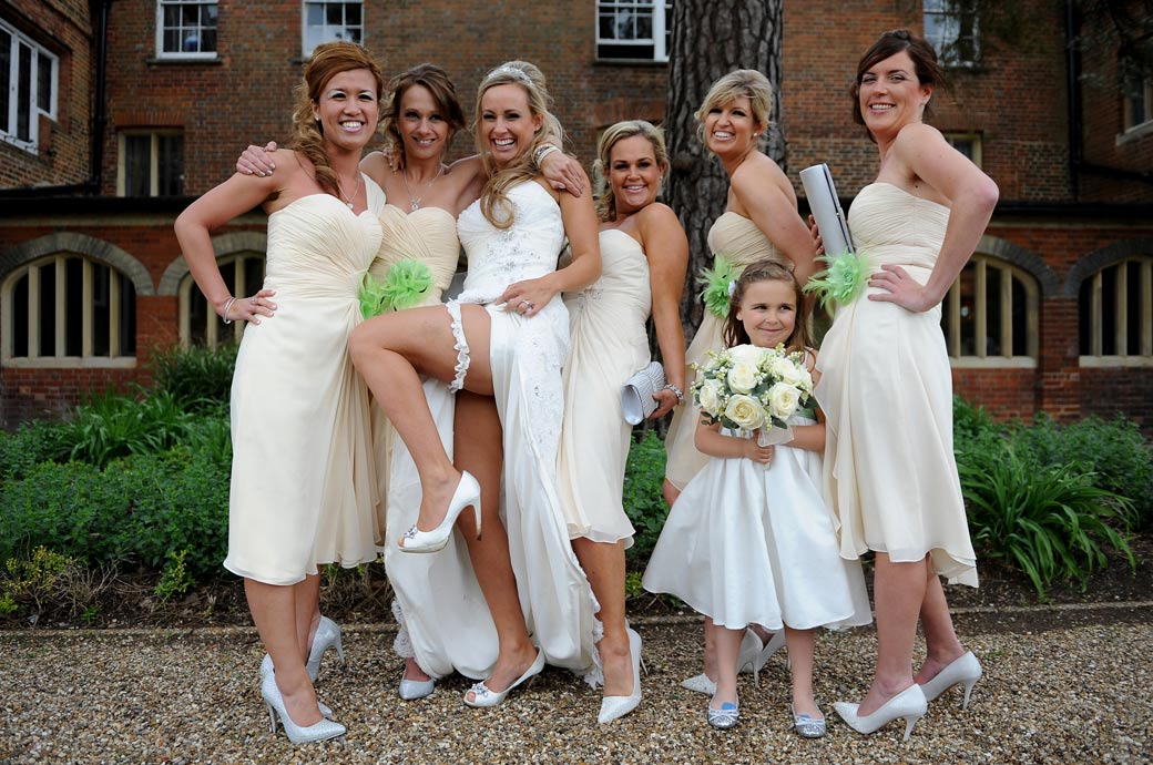 Bridesmaids having fun with the happy Bride as she shows off her garter in this saucy wedding picture captured at Wotton House in Dorking Surrey