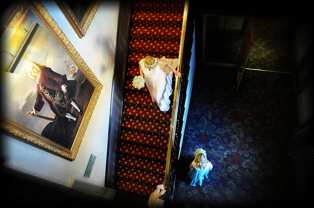 Birds eye picture of a bridesmaid walking down the stairs at  Surrey venue Wotton House in Dorking on her way to the wedding ceremony in the Old Library                                                                              at