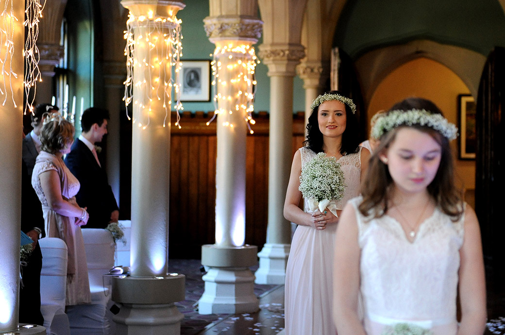 A lovely smiling Bridesmaid at Surrey wedding venue Wotton House with her garland and bouquet walking down the atmospheric aisle of the Old Library