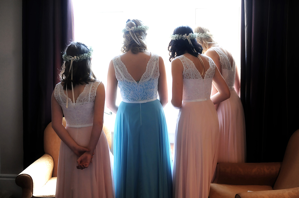 Bridesmaids at Wotton House in Dorking Surrey dressed in pink and blue dresses stand at the window watching the arriving wedding guests