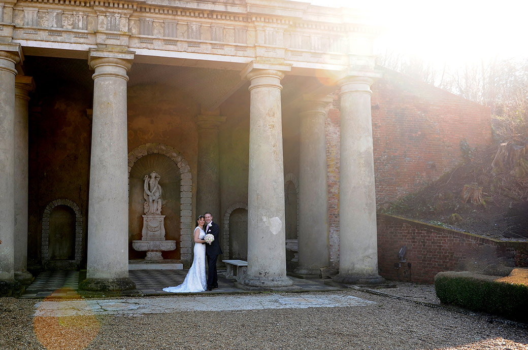 Handsome newlyweds romantically stand head to head at Surrey wedding venue Wotton House under the magnificent columns of the Roman Temple