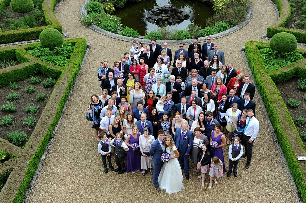 A picture of everyone at the wedding standing in front of the fountain captured from the roof of the Roman Temple at Wotton House in Dorking Surrey