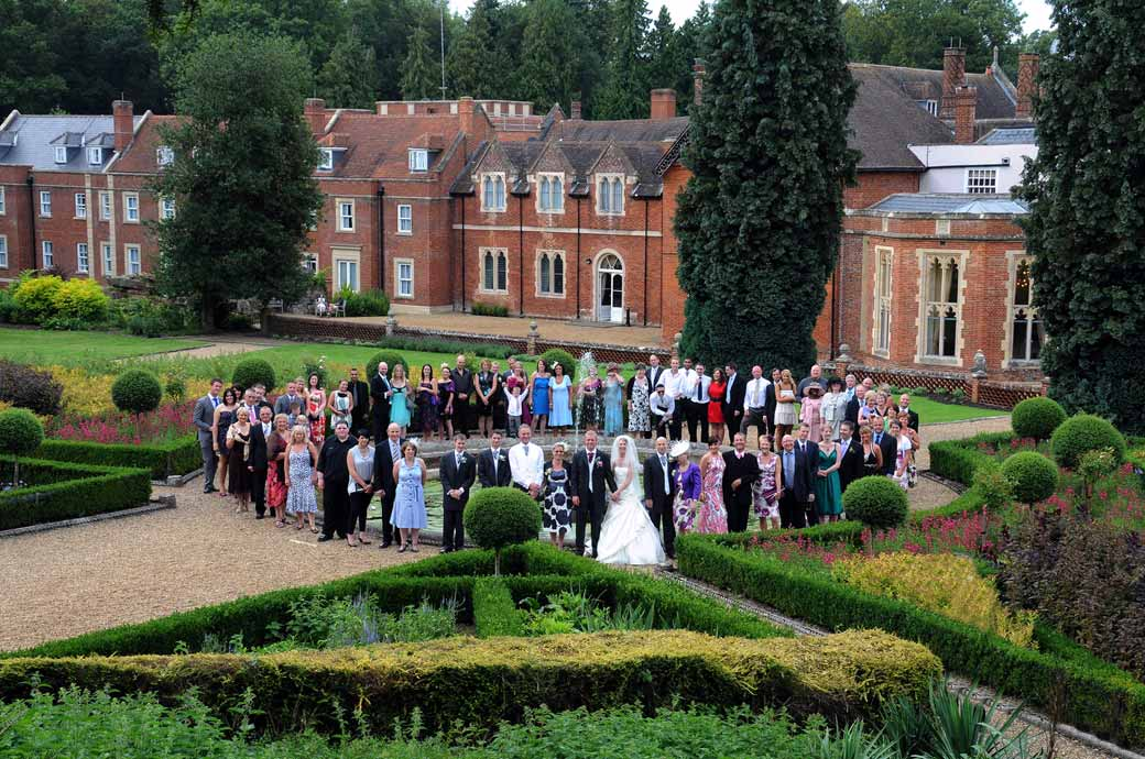 An everyone group wedding photograph taken from an ariel position up beyond the Roman style temple at Wotton House Dorking by Surrey Lane weddings