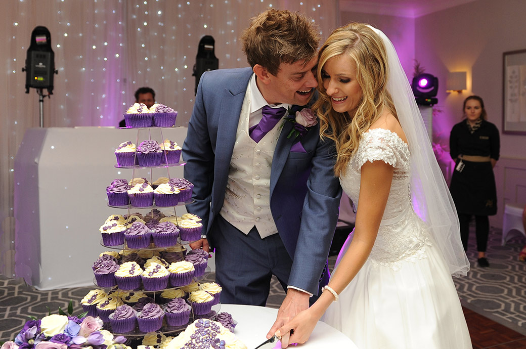 Happy wedding photo of a young handsome couple cutting their wedding cake along with the cupcakes at  Surrey wedding venue Wotton House in the Evelyn Suite
