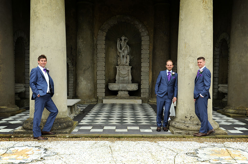 Groom and Groomsmen in blue suits strike a pose in their wedding photo by the columns of the Roman Temple in Dorking at Surrey wedding venue Wotton House