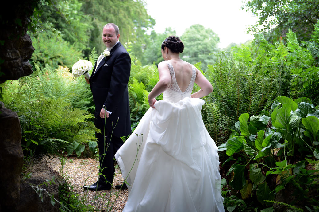 The Groom waiting for his wife as they approach one of the two grade ll listed grottos in this relaxed wedding photograph taken in the grounds of Wotton House in Dorking Surrey