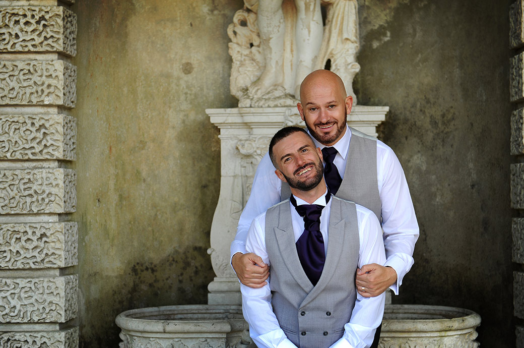 Smart and happy Grooms share a moment after their wedding at Wotton House in Dorking Surrey with a walk to the magnificent Roman Temple