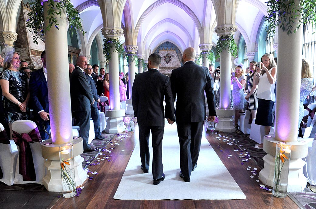 Sweet picture of two grooms at Surrey wedding venue Wotton House walking down the aisle of the Old Library hand in hand