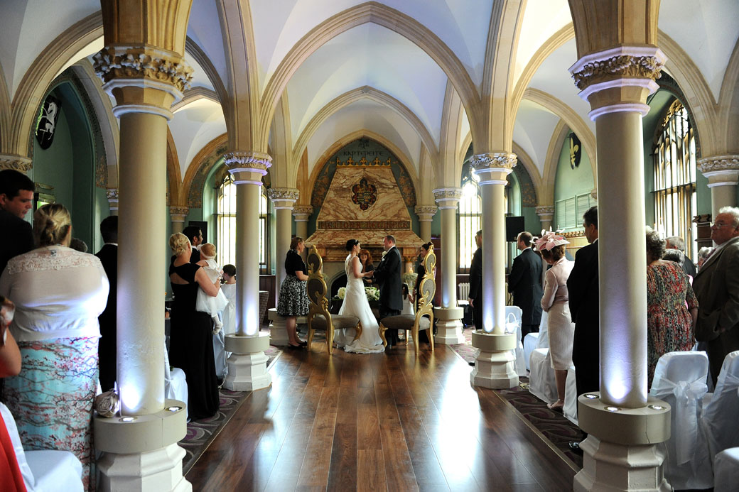 Long view down the aisle in this atmospheric wedding photograph of the Bride and Groom holding hands as they are married at Wotton House Dorking in Surrey