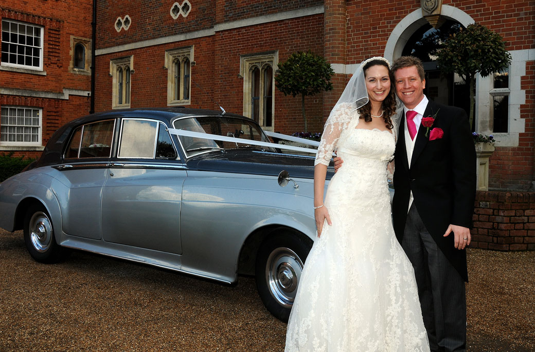 Smiling newly-wed couple standing in front of their lovely silver Rollos Royce in this wedding photography taken at Surrey wedding venue Wotton House in Dorking