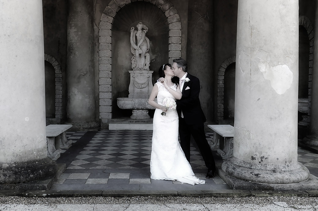 Wedding picture of a Bride and Groom passionately kissing between the columns of the wonderful Roman Temple at Wotton House a Surrey wedding venue in Dorking
