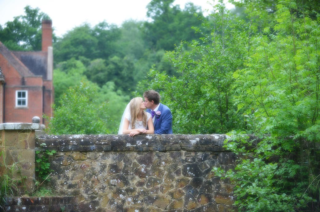 Romantic wedding picture of a Bride and groom at Surrey wedding venue Wotton House kissing on a stone bridge