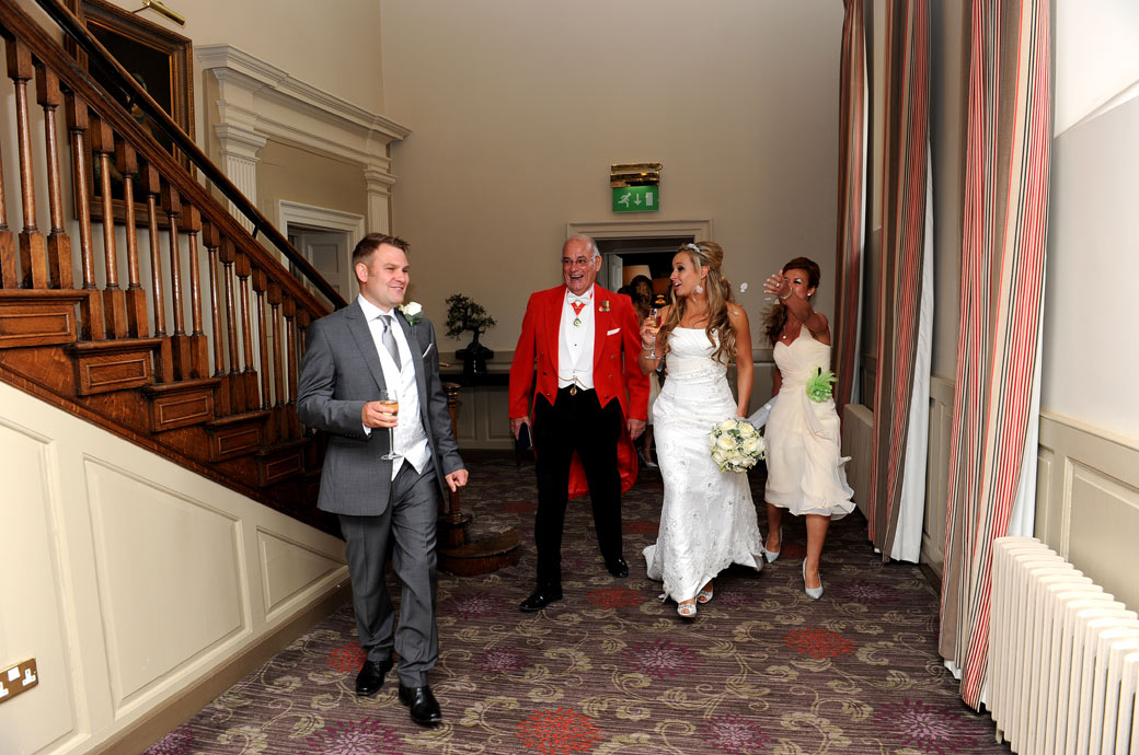 Happy celebrating newlyweds laughing captured in this wedding picture as they walk from the Old Library at Wotton House Dorking by  Surrey Land wedding photographers