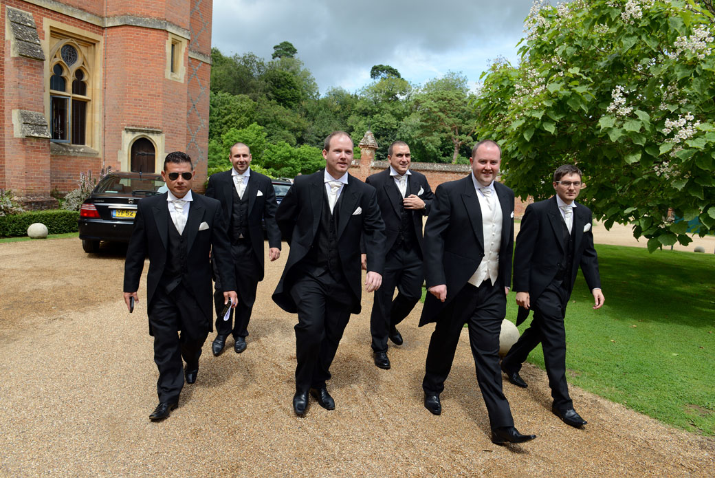 Groomsmen march along with the Groom ready for the start of the big day in this wedding photo captured by Surrey Lane wedding photographers at Wotton House in Dorking