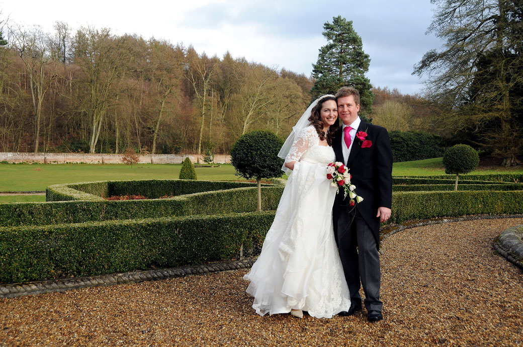 Relaxed smiling newlywed couple posing in this wedding picture at Surrey wedding venue Wotton House in the wonderful garden around the Roman Temple
