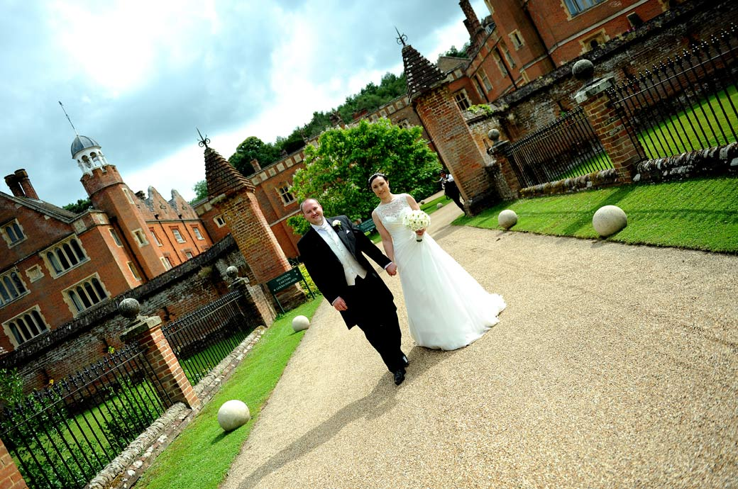 Relaxed wedding picture of the Bride and Groom walking down the main drive in front of the impressive 17th century Wotton House a fabulous Surrey wedding venue in Dorking