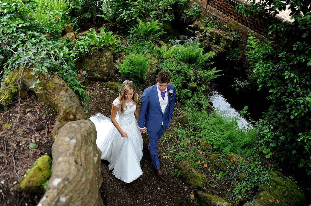 Bride and groom walking hand in hand captured from the top of one of the fascinating Grottos at Surrey wedding venue Wotton House in Dorking