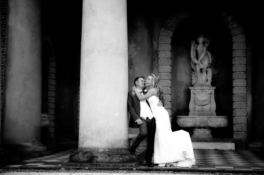 Laughing Bride hugs her handsome Groom as he leans relaxed on a temple column at the Wotton House Dorking an impressive and popular Surrey wedding venue in Dorking