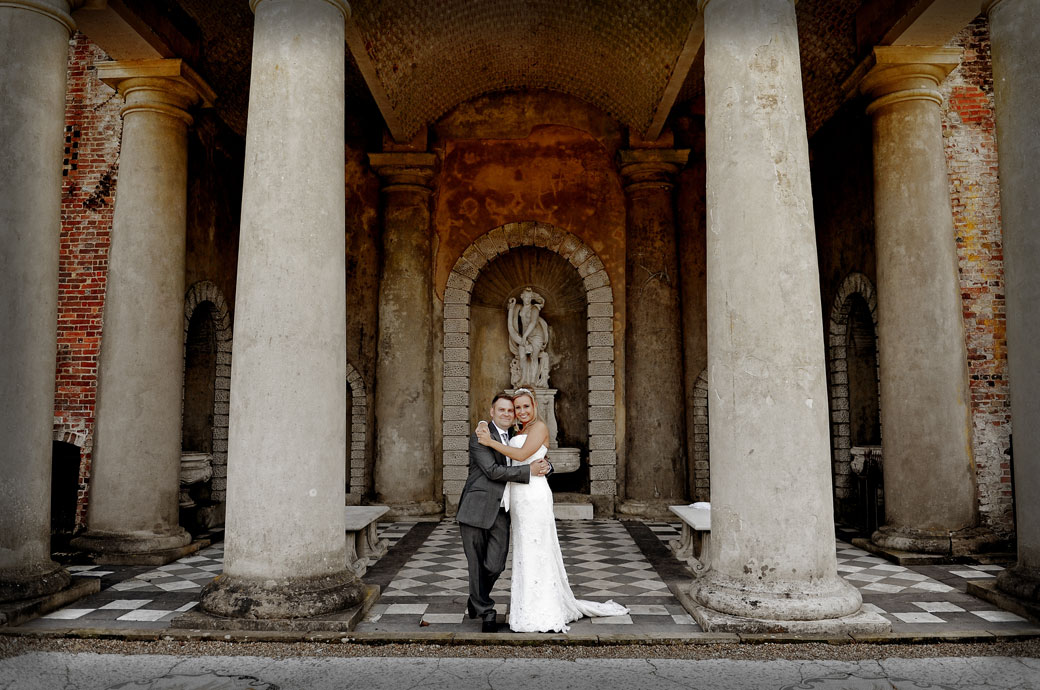 In each others arms smiling as they stand beneath the columns of the temple in this sweet wedding photograph taken at the wonderful Wotton House in Dorking Surrey