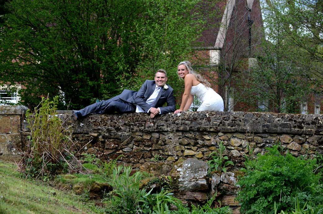 Relaxed smiling newlywed couple make themselves comfortable on the quaint bridge in the beautiful gardens in this wedding picture taken in Surrey at Wotton House Dorking