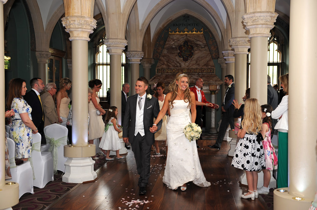 Happy and excited newlywed couple walk down the aisle of the Old Library as husband and wife at Wotton House Dorking captured by Surrey Lane wedding photographers