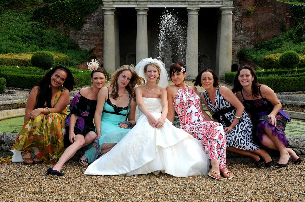 A relaxed, colourful and fun wedding photograph of the Bride and her Hen ladies posing in front of the fountain taken at Wotton House  Dorking Surrey