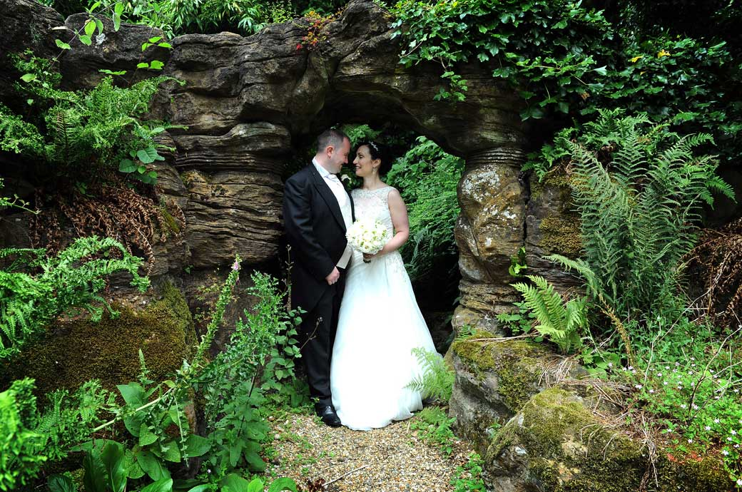 Bride and Groom share a romantic moment in this discrete wedding photograph taken by Surrey Lane wedding photography at one of the Wotton House grade ll listed grottos