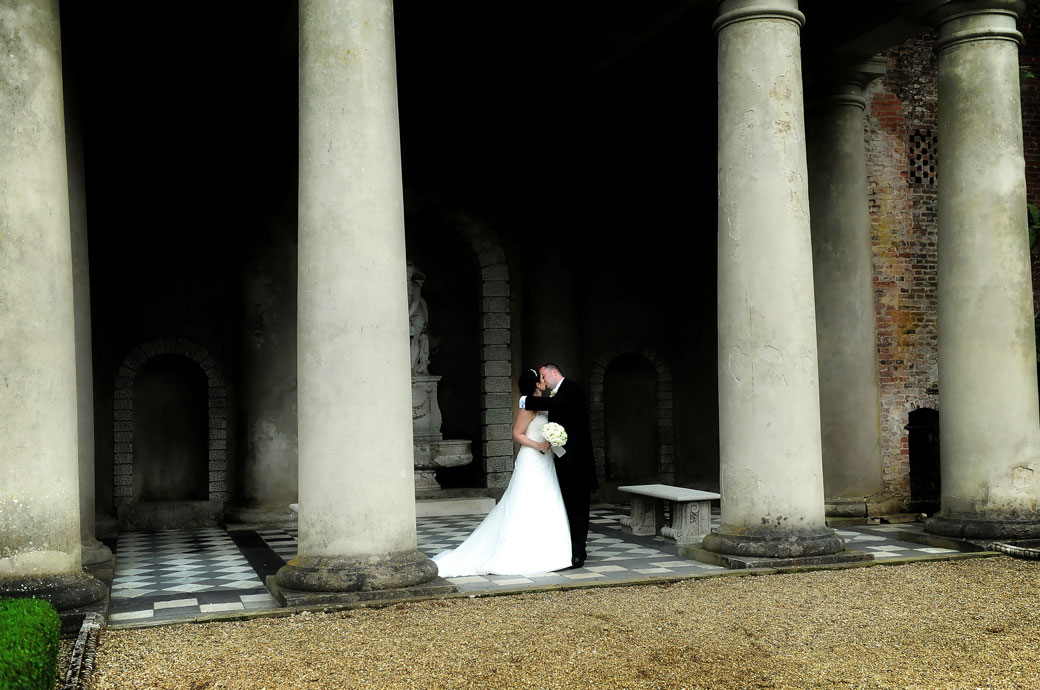 A discrete wedding photo of newly-weds having a romantic kiss in front of the pillars of the Roman Temple at Wotton House by a Surrey Lane wedding photographer