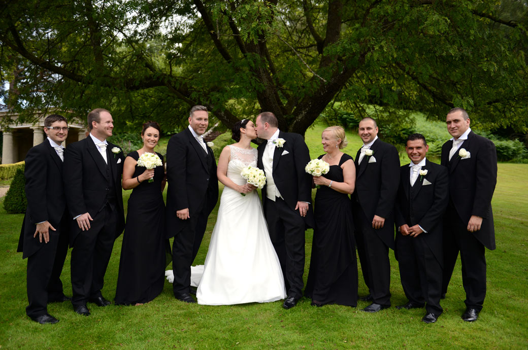 All smiles as the Bride and Groom kiss in this relaxed and informal group wedding picture by Surrey Lane wedding photographers in Dorking on the lawn at Wotton House