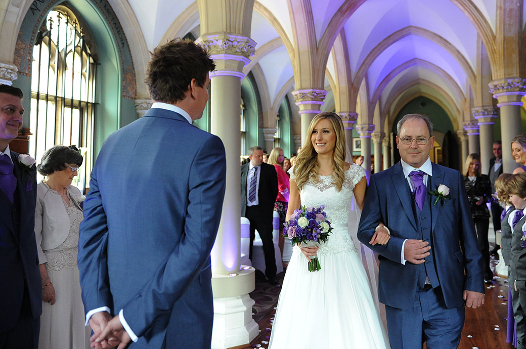 Beautiful Bride on her father's arm at  Surrey wedding venue Wotton House in Dorking smiles at her groom in the Old Library as she comes to the end of the aisle