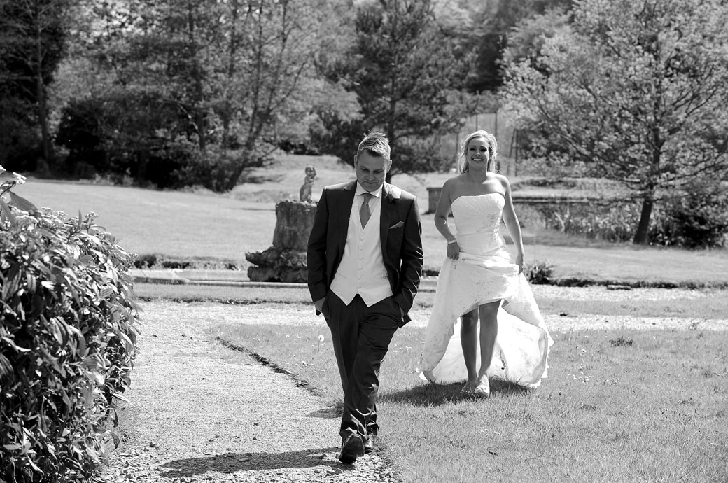 Bride smiling as she hitches up her wedding dress and follows her husband across the lawn at Wotton House Dorking captured by a Surrey Lane wedding photographer