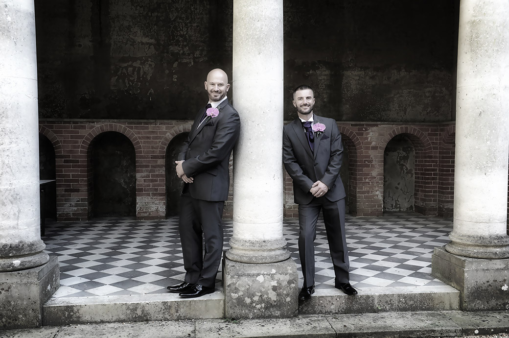 Happy smiling Grooms captured at Surrey wedding venue Wotton House in Dorking as they lean up against the tall columns of the wonderful Roman Temple