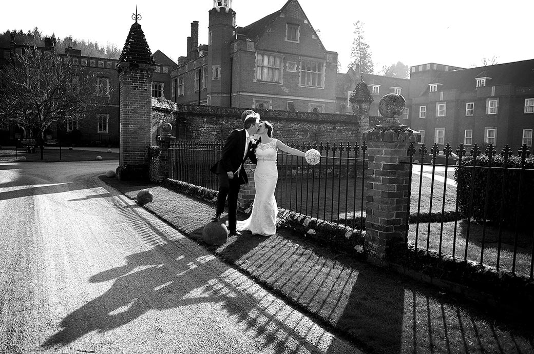 Lovely romantic wedding photograph taken at Surrey wedding venue Wotton House of a newlywed couple kissing as the sunshine creates shadows on the drive