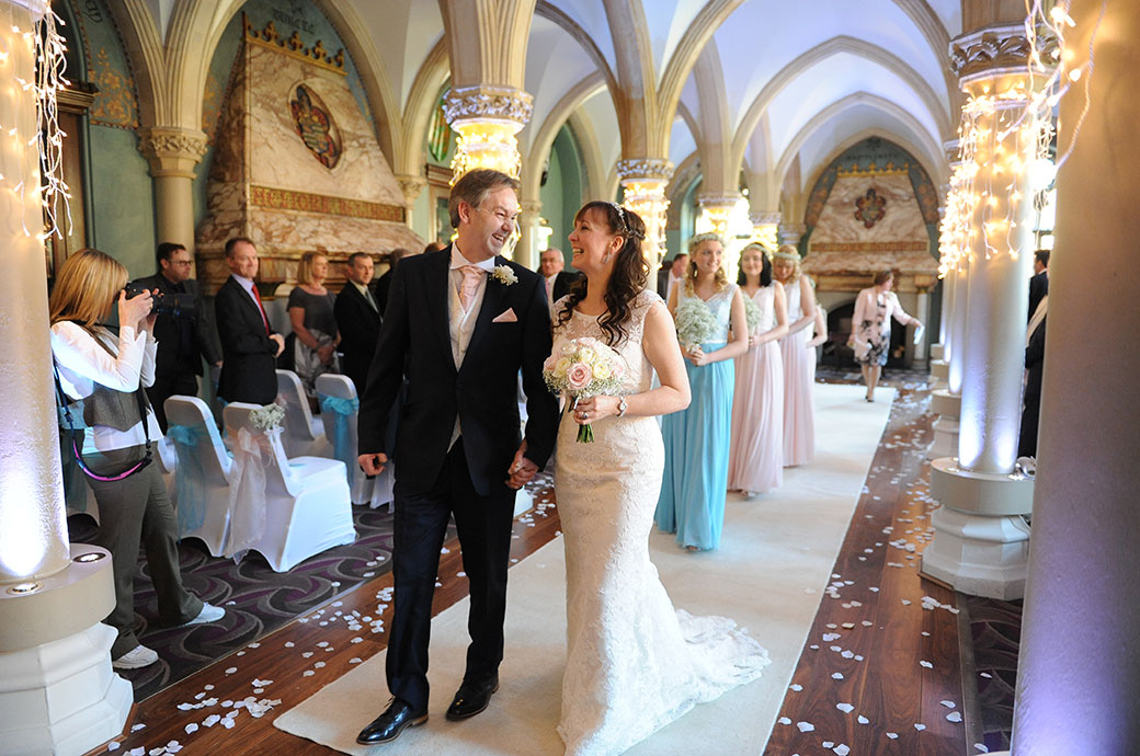Joy and delight for the Bride and Groom at Wotton House in Dorking Surrey as they walk down the aisle as husband and wife