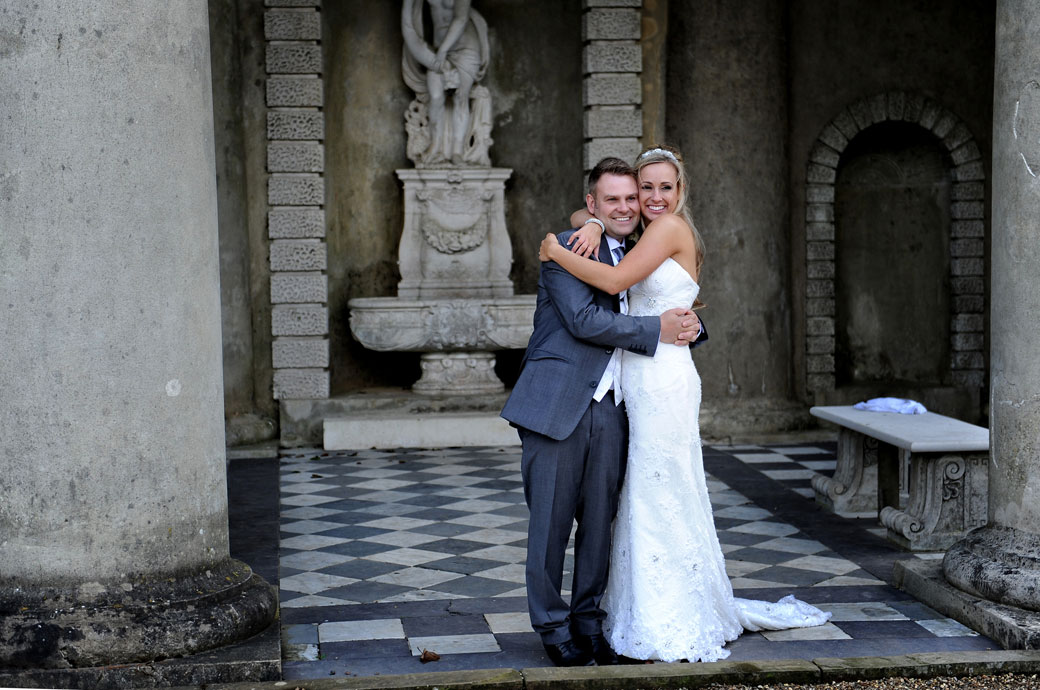 Close up wedding picture of a very happy Bride and Groom smiling and hugging each other under the impressive columned temple at Surrey wedding venue Wotton House