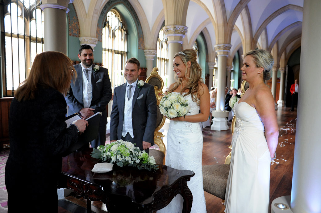 A smiling Bride and Groom as they stand with their witnesses before the marriage registrar in the Old Library at Surrey wedding venue Wotton House Dorking