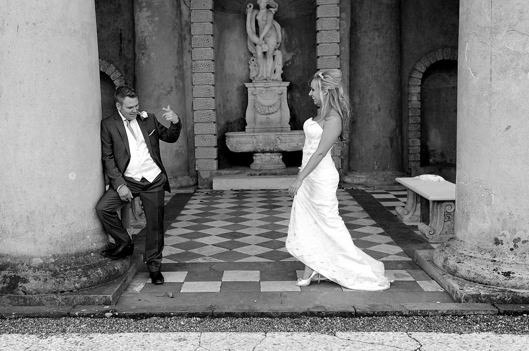 Groom beckoning his laughing Bride over to him beneath the columns of the impressive temple at the relaxed and popular Surrey wedding venue Wotton House