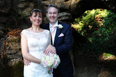 Smiling happy newlyweds enjoying the themselves at the wonderful Wotton House Surrey wedding venue as they stand in front of one of the fascinating and historic grottos
