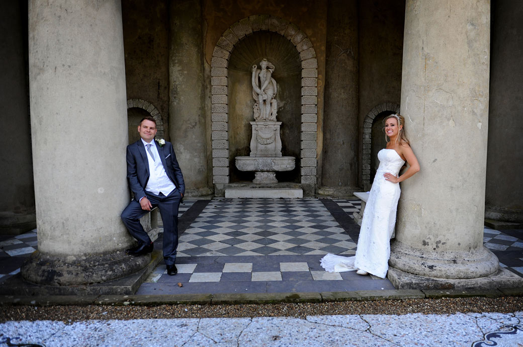 Relaxed Bride and Groom wedding picture taken of them leaning on the columns of the temple in the award winning gardens at Wotton House Dorking Surrey