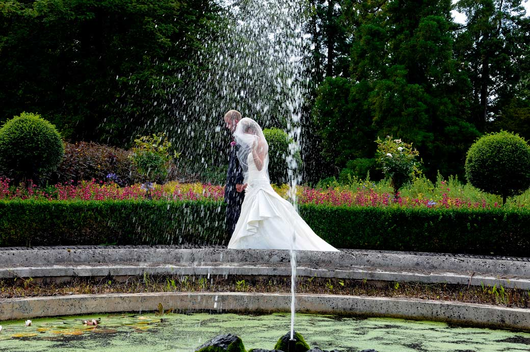 Bride and Groom in this discrete wedding photograph captured through the spray of the fountain at the lovely Surrey wedding venue at Wotton House Dorking
