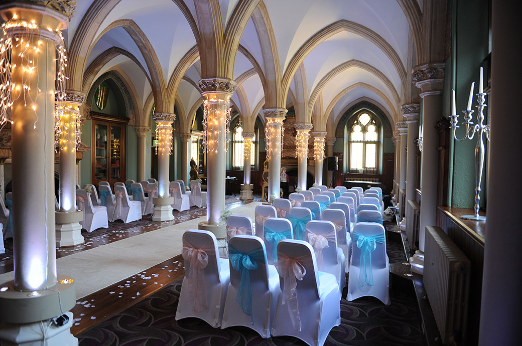 Atmospheric wedding picture of the Old Library at Surrey wedding venue Wotton House in Dorking dressed with fairy lights and pink and blue chair sashes