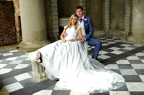 An in love Bride and Groom relax stretched out on a stone seat in the wonderful Roman temple after their marriage at  Surrey wedding venue Wotton House wedding in Dorking