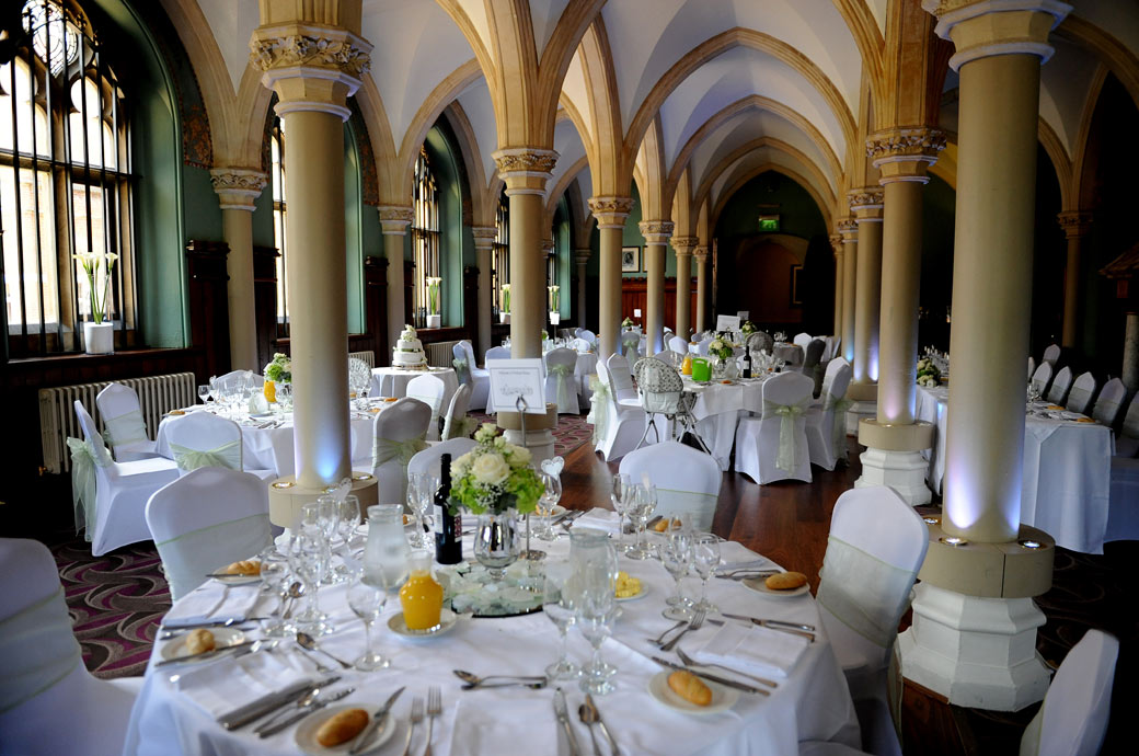 A wedding photo of the beautiful vaulted ceilinged Old library at Wotton House in Dorking Surrey set out for the wedding breakfast and awaiting the arrival of the guests
