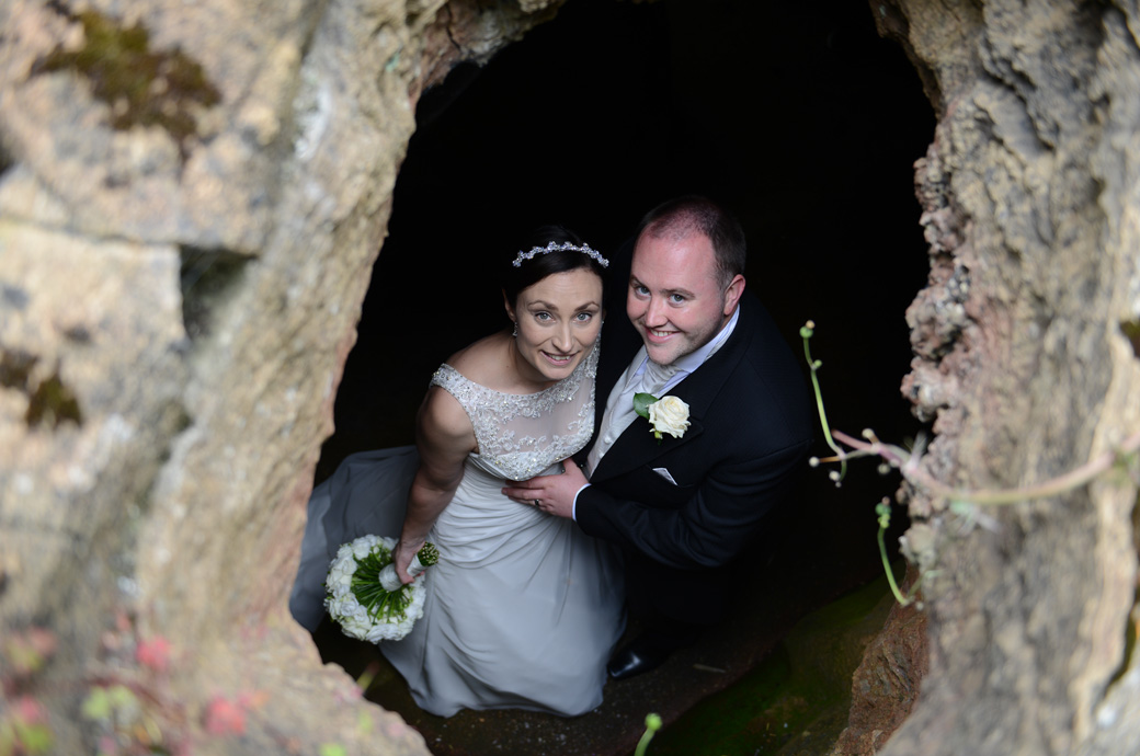 Bride and Groom look up through a hole in the ceiling of one of the grade ll listed grottos in this wedding picture taken in the wonderful Surrey wedding venue Wotton House