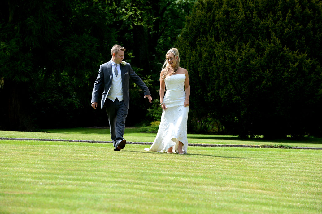 Happy relaxed Bride and groom captured in this wedding photo as they walk across the extensive lawn in the bright sunshine at the lovely Wotton House Dorking Surrey