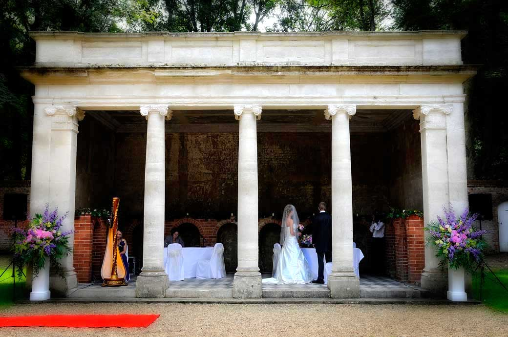 Beautiful wedding photograph of an outside wedding service in the Turtle Room captured by Surrey Lane wedding photography at Wotton House Dorking